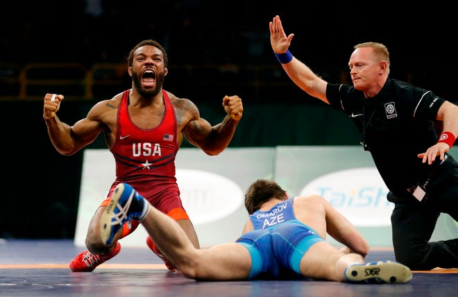 Jordan Burroughs, left, celebrates after pinning Azerbaijan's Gasjimurad Omarov, right, in their 74 kg match in the Freestyle Wrestling World Cup in 2018.