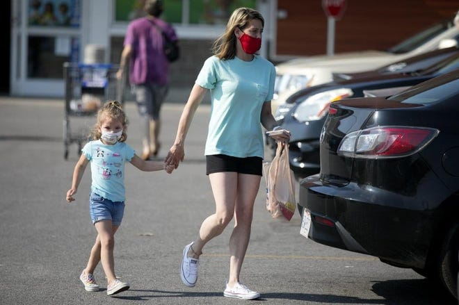 Wearing their masks, Heather Eussert and her 3-year-old daughter, Addlee Griffin, walk back to their car after shopping at Kroger in Lancaster last Friday. Getting comfortable with one's mask sometimes takes practice.