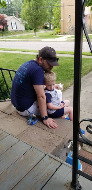 Luke Rondeau, 29, of Romeo sits outside with his son, Gavin, 3. Rondeau said he is spending more quality time with his son while he is working from home because of the pandemic. Credit: The Rondeau family