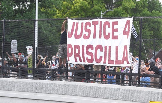 A banner is put on the overpass at I-94 during a march for Priscilla Slater in Harper Woods Wednesday evening.