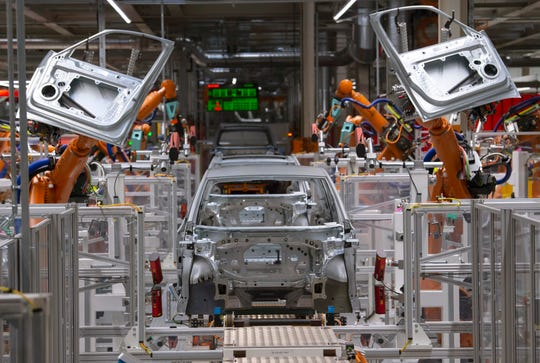 Robots work on an electric car ID.3 body at the assembly line at the plant of the German manufacturer Volkswagen AG (VW) in Zwickau, Germany on Feb. 25, 2020.