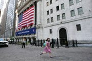 A girl wearing a mask runs by the New York Stock Exchange during the coronavirus pandemic, Thursday, July 9, 2020, in New York.
