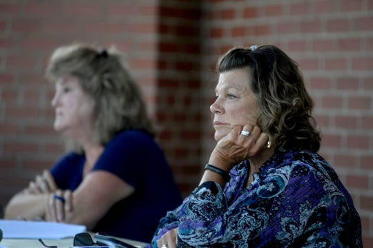 Allendale Township boardmembers Barb Vanderveen and Candy Kraker listen to people speak on the issue of removing a Civil War statue from the township park.