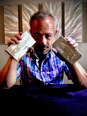John Perri withtwo 100 oz. bars of pure silver.