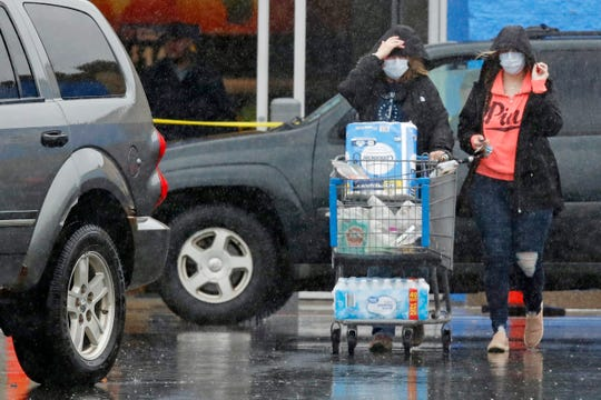 Two shoppers wearing protective masks, due to the virus outbreak, walk to their vehicle during a heavy rain storm after shopping at the Walmart store in Epping, N.H., Monday, April 13, 2020.