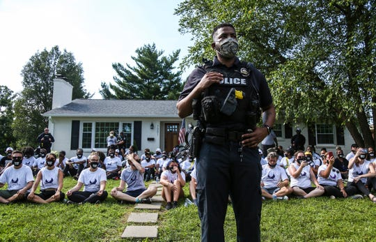 In this image from video, a Louisville Metro Police Department office stands guard outside the home of Kentucky Attorney General Daniel Cameron as protestors sit in his front yard in Louisville, Kentucky Tuesday, July 14, 2020.