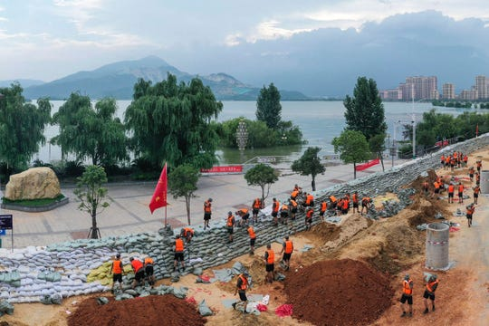 Chinese soldiers build a temporary embankment to contain Poyang Lake which has reached a record level threatening to flood Lushan city in central China's Jiangxi province Monday, July 13, 2020. Chinese authorities forecasted heavy rain across a wide swath of the country prompting evacuation of residents and raising emergency alerts levels.