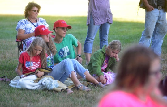 Allendale residents wearing Trump hats listen to people speak on the issue of the possible removal of a Civil War statue from a township park during an outdoor township council meeting.