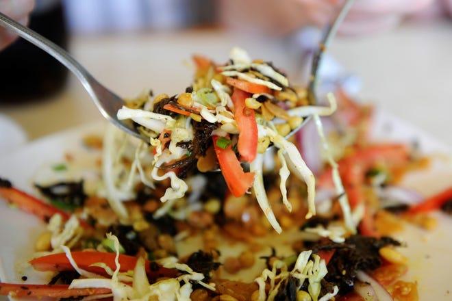 Ensalada de hojas de té con cebollas verdes, cebollas en rodajas, hojas de té fermentadas, tomates, repollo, chiles y nueces y semillas tostadas en el restaurante Owensboro Karen.