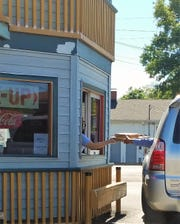A customer picks up two pizzas at the drive-through window at Turoni's Forget Me Not Inn on Monday, July 14. Turoni's has shut dining rooms and gone back to drive-through service only.
