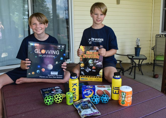Brothers Kevin and Eli Wallace sit on the back porch of their Woodville home with just a small portion of the activity supplies and snacks they received as part of this year's virtual Camp Wildcats.