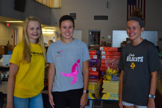 From left, Woodmore senior Kelsi Szakovits, Woodmore graduate Maddie Thatcher, and Woodmore senior Olivia Thatcher helped with prep work for this year's virtual Camp Wildcats.