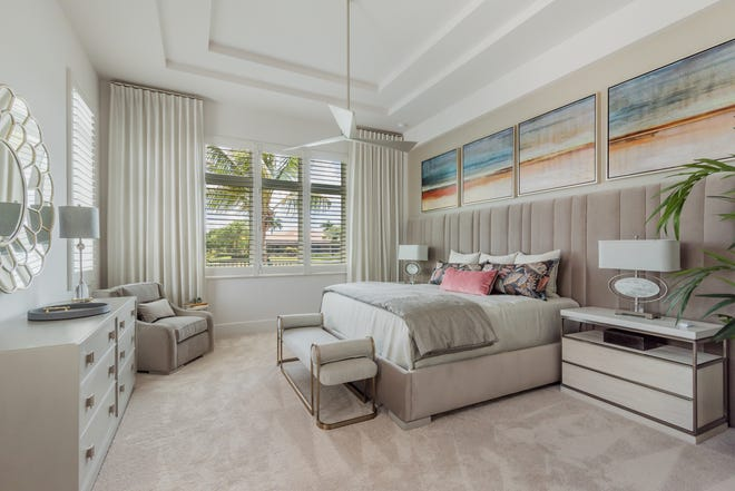 The master bedroom has a headboard that extends far beyond the bed and continues behind the night tables with art work designed for the room.