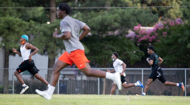 Players run while spread out across the field Tuesday, July 14, 2020, during the first day of football practice at Ridgeway High School in Memphis. Tuesday was the first day Shelby County Schools sports teams are allowed to practice since the beginning of the COVID-19 pandemic.