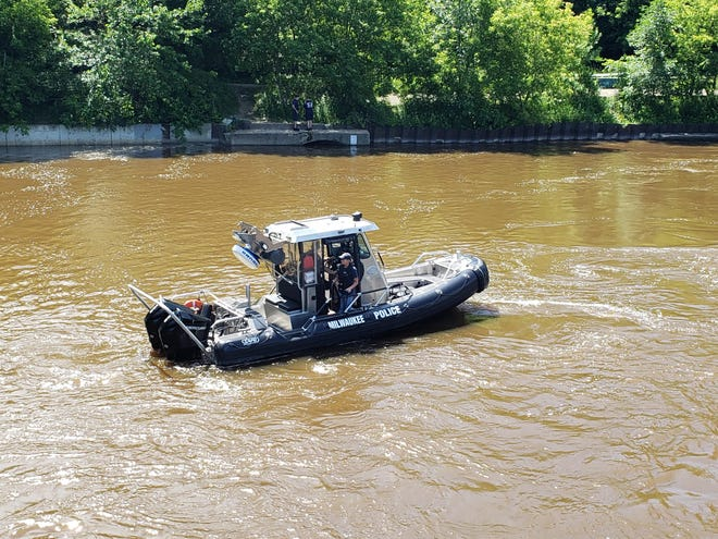 A Milwaukee Police Department boat crew searches the Milwaukee River Monday for a missing man. Authorities recovered a body there Tuesday evening.