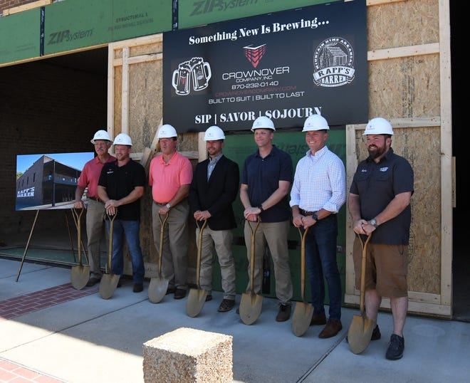 Local officials, contractors and personnel from Rapp's Barren Brewing Company pose for photos at a ceremonial groundbreaking ceremony at the Baker Building in downtown Mountain Home on Monday afternoon.