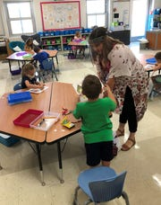 John Clem Elementary second grade teacher Ashley Williams works with students on their art Tuesday at Legend Elementary, during the Kindergarten Readiness Academy for Newark City Schools.