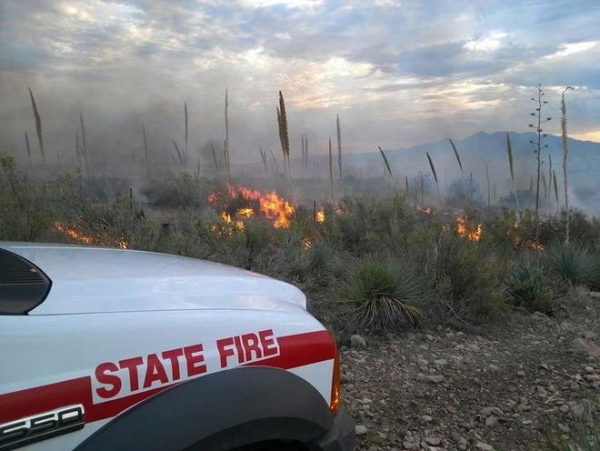 An Arizona Department of Forestry and Fire Management fire engine stays behind to monitor the fire activity and smoke at the Navarro Fire.