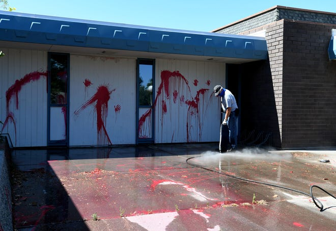 A city employee power washes the paint off the a Sparks City Hall patio after it was vandalized over night on Wednesday morning July 15, 2020.