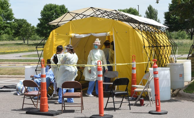 Health care workers gather in a tent during a lull in testing at the curbside collection facility Wednesday, July 15, 2020, at CentraCare Health in St. Cloud.