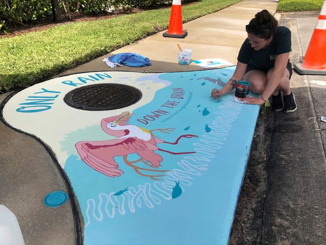 Artist Deanna Derosia, owner and creator of Sealacanth Studios, paints a Roseate spoonbill on a storm drain cover at the Indian River County Administration building. The project will expand to include four more drain covers by the end of 2020.  More are planned in 2021.