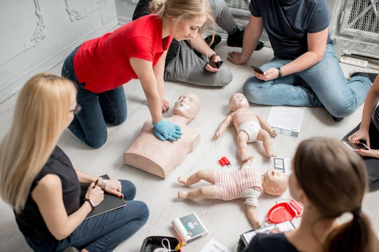 An instructor shows how to make chest compressions with dummy during a first aid group training.