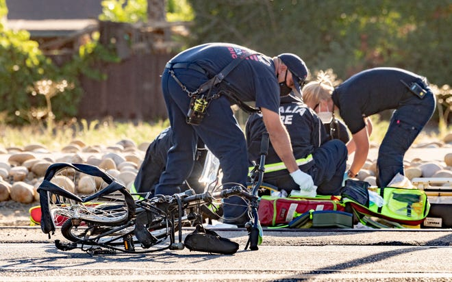 First responders work on a cyclist as Visalia Police investigate a collision Tuesday, July 14, 2020 that sent him to the hospital in critical condition and sheared a utility pole from its base. Santa Fe Street was closed between K Road and Walnut Avenue for hours.