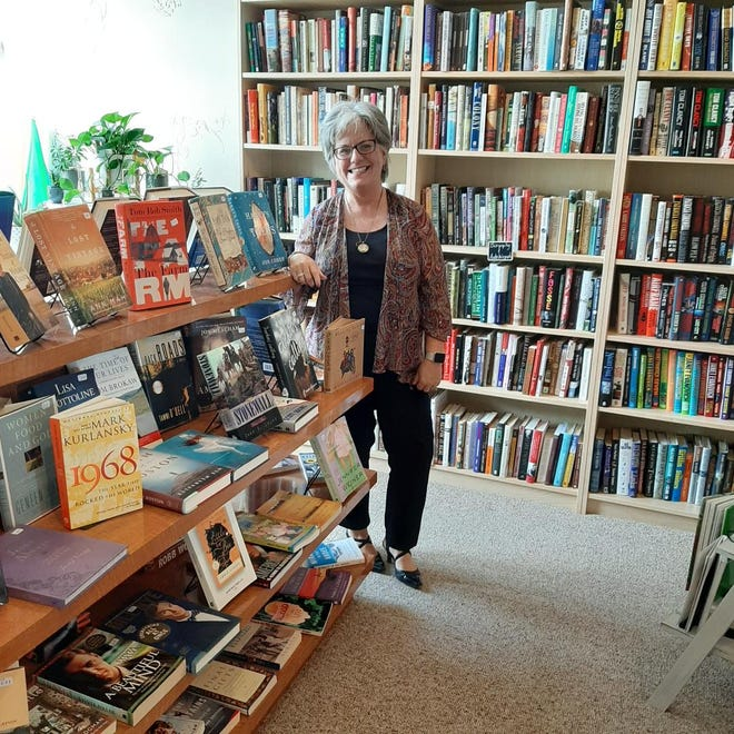 Owner Cindy Rhodes stands next to one of the book shelves that are in The Empty Nest Bookshop in New Concord.