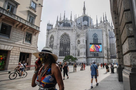 Pedestrians walk past the screen of the Duomo, showing a Moschino model during Milan Digital Fashion Week, in Milan, Italy, Tuesday, July 14, 2020. Forty fashion houses present visualizations of men's clothing for next spring and summer and pre-collections for women in digital formats due to concerns raised by COVID-19.