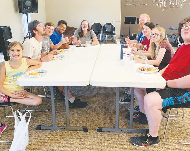 Enjoying a home-cooked meal in Haviland are students (from left) Cadie Follette, Noah Camp, Tayler Gentry, Tyree and Karalyn Singleton, Jared and Katie Werstler, and Amber and Joel Bob Hendershot. The local Follette family provides Barclay College students in the small town for summer with free eats each week.
