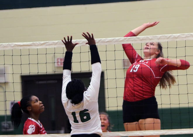Hendersonville's Emily Beeker (19) gets ready to spike the ball as East Henderson's Sontee Moore (16) defends during Tuesday's match at East. [DEAN HENSLEY/ TIMES-NEWS]