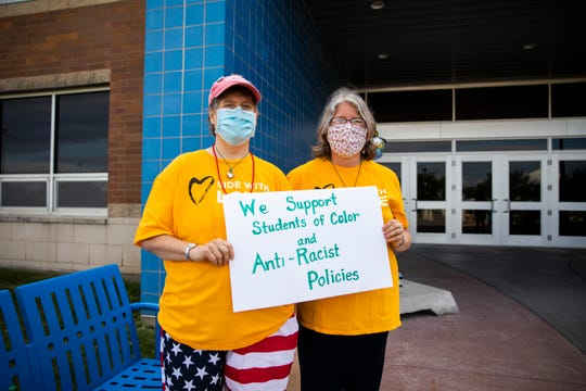 Sarah Ross, left, and Peggy Garrigues pose for a portrait before the Clear Creek-Amana school board meeting at Clear Creek-Amana High School on Wednesday, July 15, 2020. Ross and Garrigues, both members of the Unitarian Universalist Society in Coralville, stood outside of the school in support of students of color.