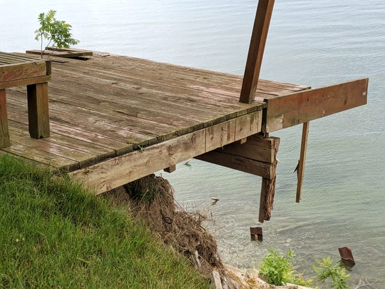 Tim Lathe's deck overlooking Lake Michigan teeters over the edge of a fast-eroding cliff at his home on Lakeshore Avenue in Ottawa County's Park Township in this July 14, 2020 photo.