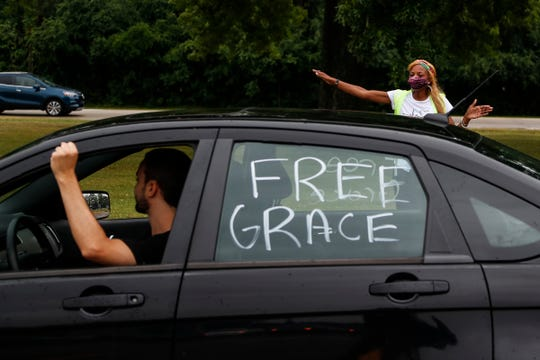 Coreen Ellis of Kalamazoo directs vehicles as they leave for the #FreeGrace car caravan and rally outside of Groves High School in Beverly Hills on July 16, 2020.