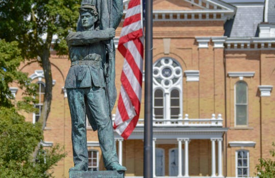 Hillsdale College's Central Hall pictured behind the backdrop of the campus's Civil War Memorial.