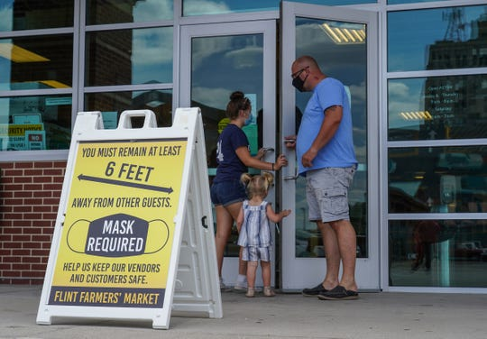 Patrons enter the Flint Farmers' Market while wearing face masks after walking by a large sign posted at the entrance stating masks required and to keep socially distanced on July 14, 2020.