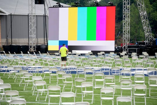 """Workers help prepare for a graduation commencement ceremony at Frank """"Muddy"""" Waters Stadium, at Hillsdale College, in Hillsdale, July 16, 2020. The college held a commencement celebration on Saturday despite concerns about COVID-19 and a warning from the state attorney general that the event would be illegal."""