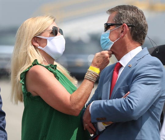Georgia Gov. Brian Kemp has his mask adjusted by first lady Marty while waiting for President Donald Trump to arrive for his Georgia visit to talk about an infrastructure overhaul at the UPS Hapeville hub at Hartsfield-Jackson International Airport on Wednesday July 15, 2020 in Atlanta.