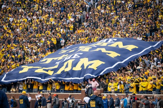 """Michigan fans hold up a large sign that reads, """"The team, the team, the team,"""" during a game against Iowa in 2019."""