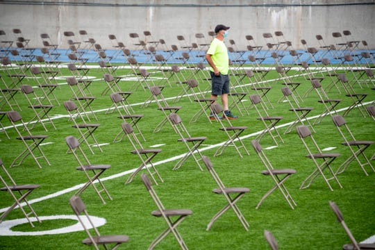 """An employee walks through hundreds of spread-out chairs lining the field in preparation for a graduation commencement ceremony at Frank """"Muddy"""" Waters Stadium, at Hillsdale College, in Hillsdale, July 16, 2020."""