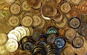 This April 3, 2013, file photo shows bitcoin tokens in Sandy, Utah. Unidentified hackers broke into the Twitter accounts of technology moguls, politicians, celebrities and major companies Wednesday, July 15, 2020, in an apparent Bitcoin scam.