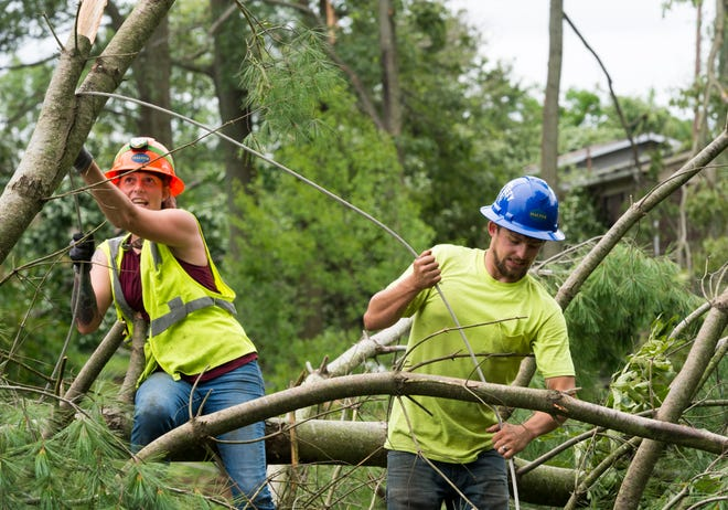 Brittney Winters, left, and Dillan Charlton, right withThe Halter Group Tree Service untangle power lines from a fallen tree in the backyard of Don Brown's home off Denzer Road in Posey County, Ind., Thursday afternoon, July 16, 2020.