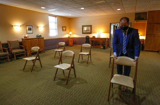 Jason Dill spaces out chairs in preparation for a funeral at Uecker-Witt Funeral Home in Fond du Lac.  Due to the coronavirus pandemic, families and funeral homes have had to face and adjust to limitations.