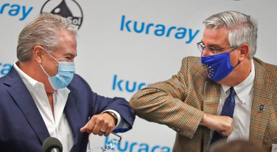 Governor Eric Holcomb, right, elbow bumps MonoSol President and CEO P. Scott Bening after speaking at the MonoSol Lebanon Facility ribbon cutting, Thursday, July 16, 2020.
