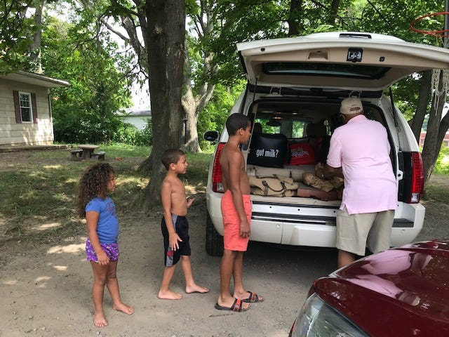 Siblings Aleya Stubbs, Sammy Stubbs and Noah Brandon of Wood Street greeted Erskine Braggs of UMADAOP Community Outreach Center Thursday for free breakfast and lunch meals. The meals are free through Aug. 7 to any Mansfield City Schools' students.