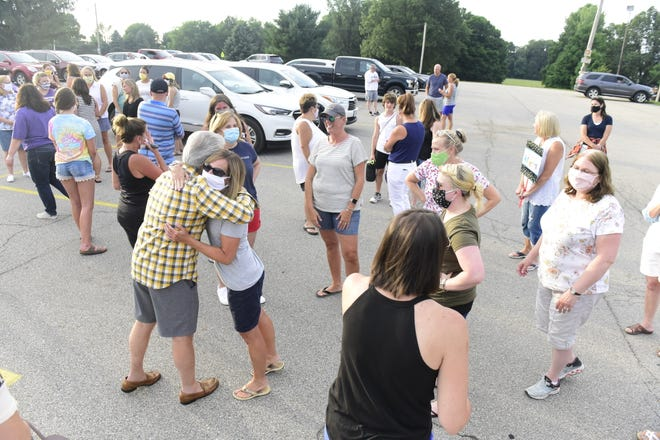 Mike Ziegelhofer gets a hug after Wednesday's school board meeting. Nearly 200 people gathered to thank him for his 32 years of service to Lexington City Schools.