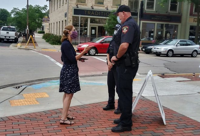 A Dane County health inspector speaks with MIddleton police officers outside of Helbachs Coffee.