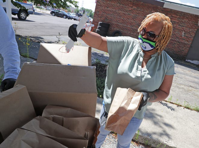 Erica Swan, with the Milwaukee Health Department prepares bags with face masks before handing them out at the City Of Milwaukee Health Department- Northwest Health Center at 7630 W. Mill Road Milwaukee  on Thursday, July 16, 2020. City residents can request and receive a free face mask at various Milwaukee Health Department locations. A mask mandate went into effect Thursday for Milwaukee that requires masks to be worn in indoor and outdoor public spaces. Themask mandaterequires anyone in the city who is at least 3 years old to have a face covering when they leave home.Masks must be worn whenever you're in a building that is open to the public and when you are outside in a public space and within 6 feet of any other person who is not your household or family member. Mike De Sisti / Milwaukee Journal Sentinel