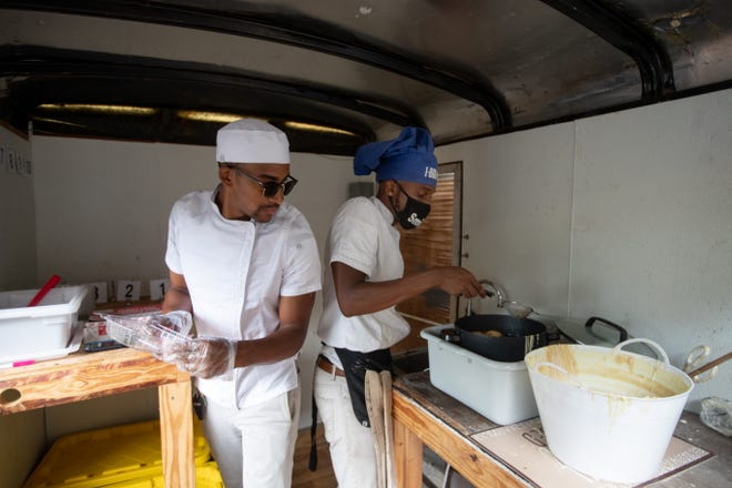 Marquis Williams, left and Demetrius Murray work together to make an order of deep-fried Oreos for a customer inside the pair's new food trailer purchased with the help of a GoFundMe Wednesday, July 15, 2020.