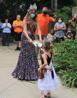 Crooksville-Roseville Pottery Festival Queen Tenessa Woods holds the plate for Princess Karly Barnhart to break during the Clay Center's 50th annual plate breaking auction on Thursday. The plate breaking was still held despite the festival being canceled in May due to the COVID-19 pandemic.